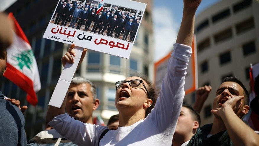 "A Lebanese anti-government demonstrator holds a sign with a photo of the Lebanese government in Arabic that reads ""Thieves of Lebanon,"" as she shouts slogans during a protest against newly approved taxes in downtown Beirut, Lebanon, Sunday, March 19, 2017. Thousands of demonstrators have descended on central Beirut to protest a broad tax hike they say is unfairly targeting the country's working classes. (AP Photo/Bilal Hussein)"