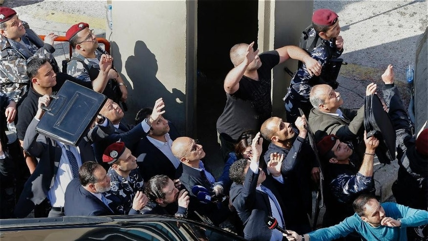 "ALTERNATIVE CROP OF XBH112 -- Bodyguards protect Lebanese Prime Minister Saad Hariri, center left with hand on mouth, from water bottles thrown by demonstrators in downtown Beirut, Lebanon, Sunday, March 19, 2017. Demonstrators pelted the prime minister's car with water bottles on Sunday as protests against new taxes and a stagnant public wage scale gained force in the city. Hariri got out of his armored convoy behind the police line at the demonstration facing the government's capital building but could get no closer as protesters began throwing water bottles and shouting ""Thieves!"" (AP Photo/Bilal Hussein)"