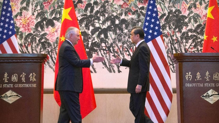 U.S. Secretary of State Rex Tillerson, left, and Chinese Foreign Minister Wang Yi reach to shake hands at the end of a joint press conference following their meeting at the Diaoyutai State Guesthouse in Beijing, China, Saturday, March 18, 2017. Tillerson pushed for closer China-U.S. cooperation on dealing with North Korea's nuclear program in his first face-to-face talks Saturday with leading Chinese diplomats. (AP Photo/Mark Schiefelbein, Pool)