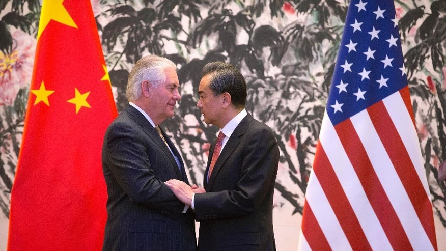 U.S. Secretary of State Rex Tillerson, left, and Chinese Foreign Minister Wang Yi stare at each other as they shake hands at the end of a joint press conference following their meeting at the Diaoyutai State Guesthouse in Beijing, China, Saturday, March 18, 2017. Tillerson pushed for closer China-U.S. cooperation on dealing with North Korea's nuclear program in his first face-to-face talks Saturday with leading Chinese diplomats. (AP Photo/Mark Schiefelbein, Pool)