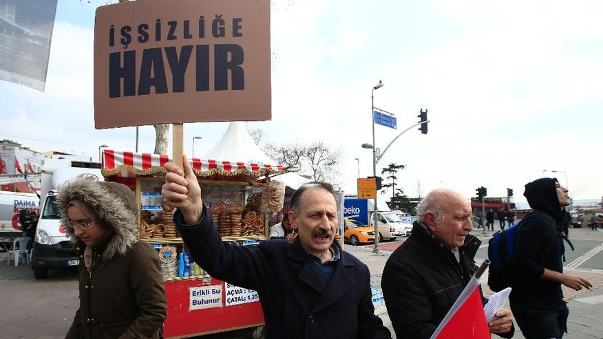 In this Wednesday, March 15, 2017 photo, a Turkish man supporting the 'NO' vote for the upcoming referendum holds a Turkish flag and a placard, reading in Turkish: 'No to unemployment' as he chants slogans in central Istanbul. The entire Turkish referendum campaign has been biased and unfair, those opposed to expanding the president's powers say, noting they have been hampered by a lack of TV airtime, threats, violence, arbitrary detentions and even sabotage. Those reports come even as Turkish President Recep Tayyip Erdogan himself has slammed European countries for not letting his ministers campaign on their soil for the April 16 vote on expanding his powers. (AP Photo/Lefteris Pitarakis)