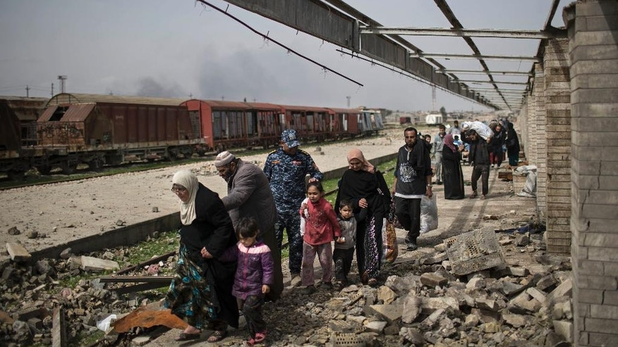 Iraqi civilians flee through a destroyed train station during fighting between Iraqi security forces and Islamic State militants, on the western side of Mosul, Iraq, Sunday, March 19, 2017. More than 750 civilians have been killed or wounded in the first month of fighting in the Iraqi offensive to retake western Mosul from the Islamic State group, front-line medics say, a number they expect to spike as Iraqi forces push into Mosul's old city. Iraqi forces have increasingly turned to airstrikes and artillery in the heavily populated urban terrain, and impoverished residents running out of food are forced to flee their homes, making dangerous journeys across front lines. (AP Photo/Felipe Dana)