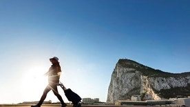 In this Wednesday, March 1, 2017 photo, a woman walks on the Spanish side of the border between Spain and the British overseas territory of Gibraltar with the Rock as a background, in La Linea de la Concepcion, Southern Spain. As Gibraltar braces itself to be dragged out of the European Union along with the United Kingdom, the livelihoods of nearly 300,000 people living in an economic region spanning two countries, have been thrown up in the air. (AP Photo/Daniel Ochoa de Olza)