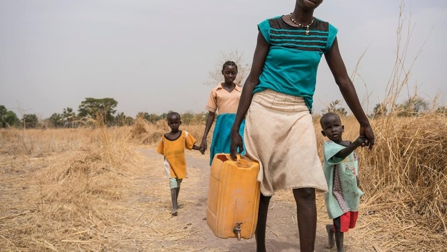 In this photo taken Sunday, March 12, 2017, a girl Abuk walks home with her brothers and friends after collecting clean water from a water point four kilometers away from her home, in Aweil, in South Sudan. As World Water Day approaches on March 22, more than 5 million people in South Sudan, do not have access to safe, clean water, compounding the problems of famine and civil war, according to the UNICEF. (Mackenzie Knowles-Coursin/UNICEF via AP)