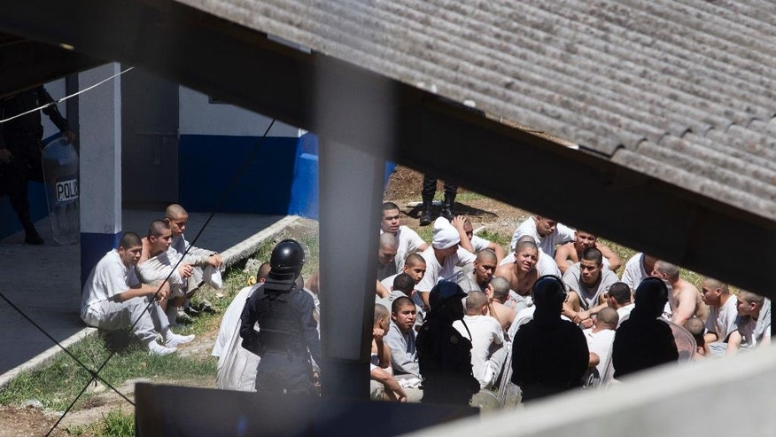 Inmates sit in an area controlled by the police at the Centro Correccional Etapa II reformatory, after a prisoners riot, in San Jose Pinula, Guatemala, Monday, March 20, 2017. A riot erupted at the detention center, and authorities said several jail monitors were killed and several others have been injured. (AP Photo/Moises Castillo)