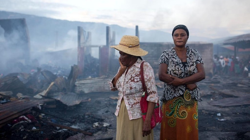 Women stand in the smoldering remains after a fire at a market in Port-au-Prince, Haiti, Monday March 20, 2017. The fire raged at the biggest central market in the center of the Capital. (AP Photo/Dieu Nalio Chery)