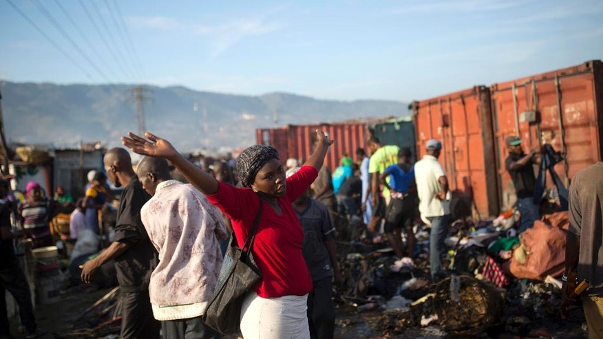 A woman stands next to to a pile a fire damaged clothing after a massive fire at a market in Port-au-Prince, Haiti, Monday March 20, 2017. The fire raged at the biggest central market in the center of the Capital. (AP Photo/Dieu Nalio Chery)