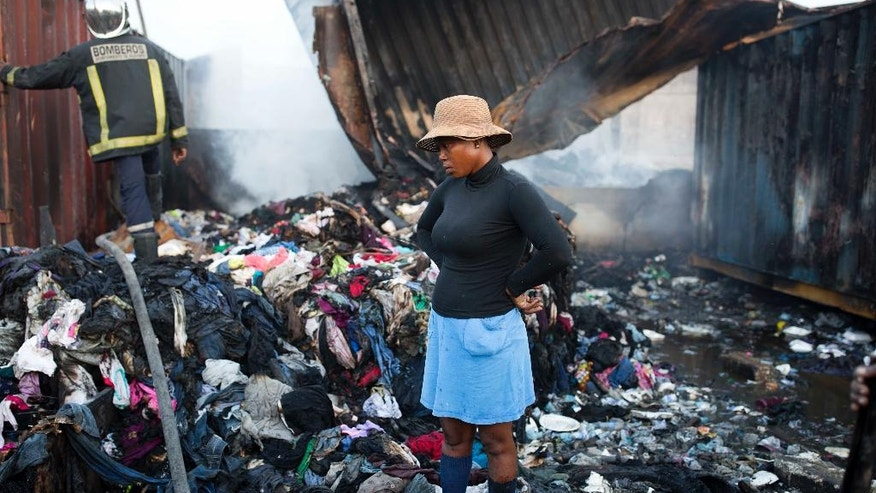 A woman stands in the middle of her fire damaged clothes after a massive fire at a market in Port-au-Prince, Haiti, Monday March 20, 2017. The fire raged at the biggest fish and clothing market in the center of the Capital. (AP Photo/Dieu Nalio Chery)