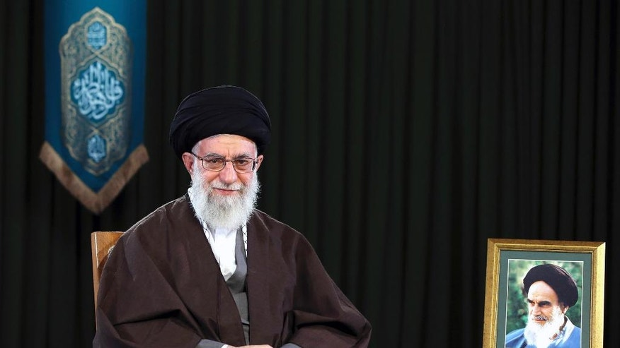 In this picture released by official website of the office of the Iranian supreme leader on Monday, March 20, 2017, Supreme Leader Ayatollah Ali Khamenei sits in a session to deliver his message for the Iranian New Year, Iran. Nowruz, a festival to celebrate the new Persian year starts with the spring. Iranians follow the Persian solar year, and this year, they begin the year 1396. A portrait of the late revolutionary founder Ayatollah Khomeini is placed at right. (Office of the Iranian Supreme Leader via AP)
