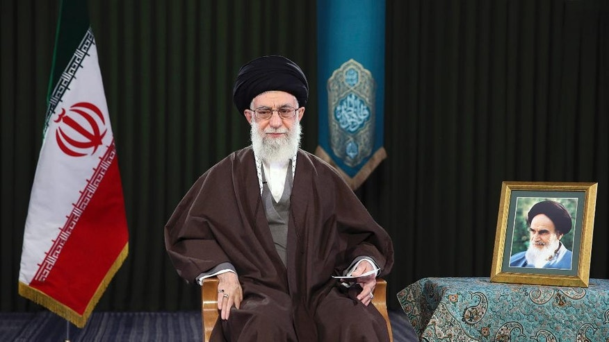 In this picture released by official website of the office of the Iranian supreme leader on Monday, March 20, 2017, Supreme Leader Ayatollah Ali Khamenei sits in a session to deliver his message for the Iranian New Year, or Nowruz, Iran. Nowruz, a festival to celebrate the new Persian year starts with the spring. Iranians follow the Persian solar year, and this year, they begin the year 1396. A portrait of the late revolutionary founder Ayatollah Khomeini is placed at right. (Office of the Iranian Supreme Leader via AP)