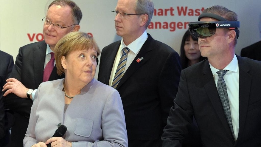 German Chancellor Angela Merkel, left, looks at a man wearing virtual reality glasses during a visit at the booth of Vodafone as part of a walkabout at the IT trade fair CeBIT in Hanover, Germany, Monday, March 20, 2017. (AP Photo/Jens Meyer)