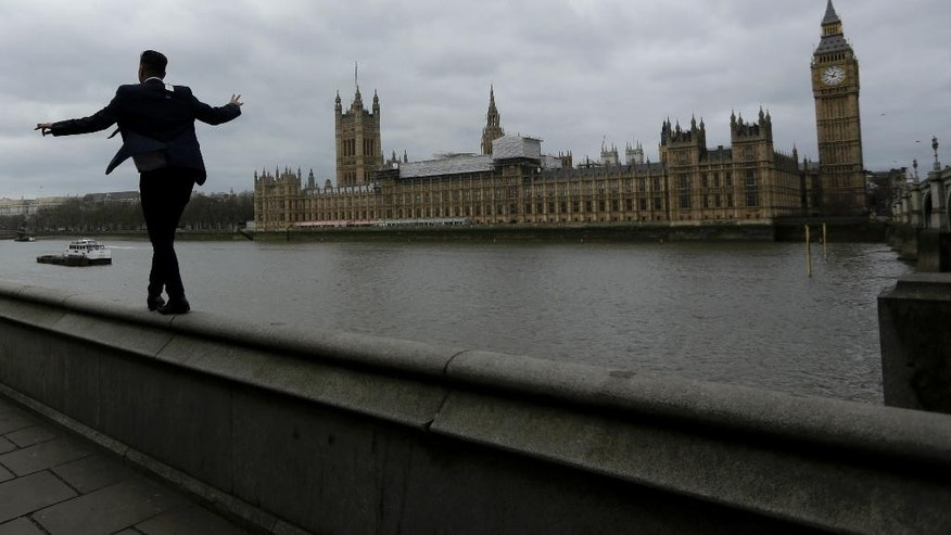 "A man balances as he walks along a wall above the River Thames backdropped by the Houses of Parliament and Elizabeth Tower containing the bell know as ""Big Ben"" in London, Monday, March 20, 2017. Britain's government will begin the process of leaving the European Union on March 29, starting the clock on the two years in which to complete the most important negotiation for a generation. (AP Photo/Matt Dunham)"