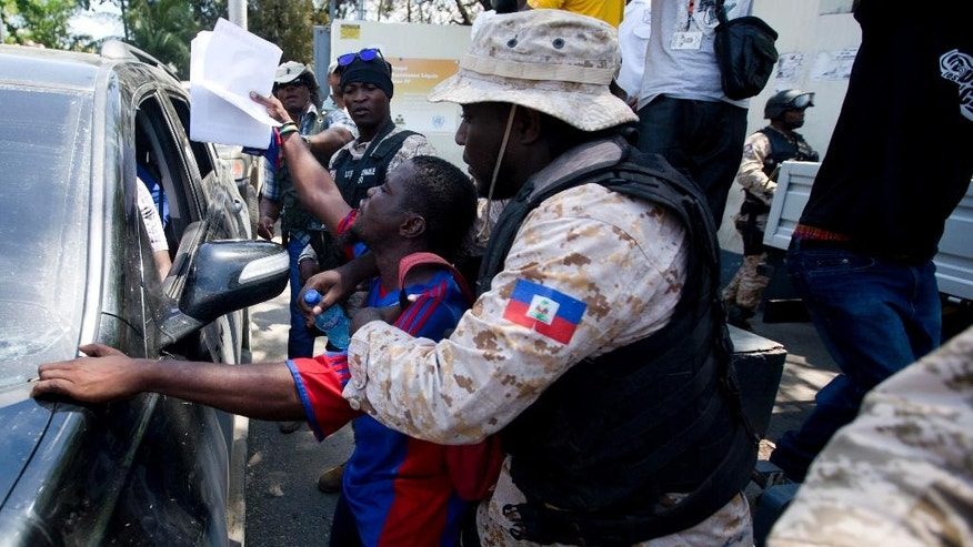 A supporter of former Haitian President Jean-Bertrand Aristide tries to cross the police barricade outside the courthouse in Port-au-Prince, Haiti, Monday March 20, 2017. Judge Jean Wilner Morin is questioning Aristide as a witness about the case of Jean Anthony Nazaire who's implicated in money laundering. ( AP Photo/Dieu Nalio Chery)