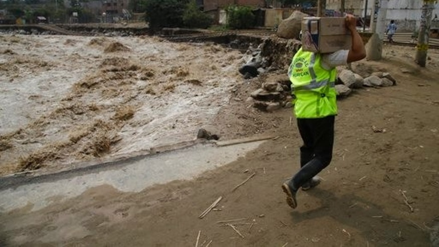 A local security officer carries a box of cookies to a shelter for those affected by flooding, alongside an overflowing river in the Chosica district of Lima, Peru, Sunday, March 19, 2017.