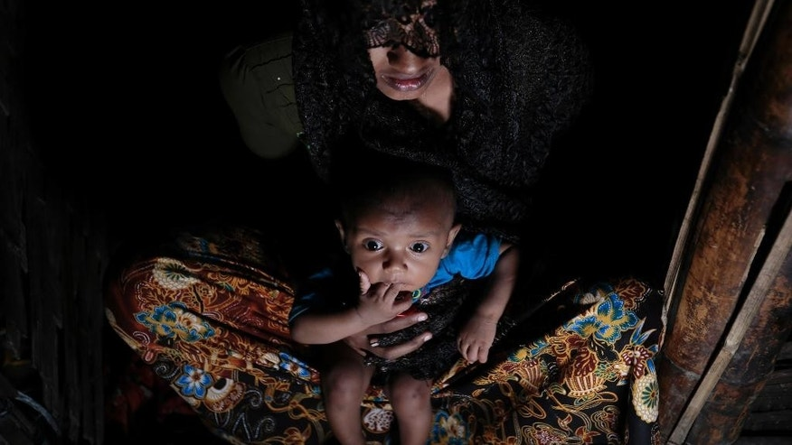 FILE- In this Dec. 2, 2016 file photo, Mohsena Begum, a Rohingya who escaped to Bangladesh from Myanmar, holds her child and sits at the entrance of a room of an unregistered refugee camp in Teknaf, near Cox's Bazar, a southern coastal district about, 296 kilometers (183 miles) south of Dhaka, Bangladesh. A Bangladesh official says an investigating team formed by Myanmar leader Aung San Suu Kyi has visited two makeshift camps in southern Bangladesh and questioned some of the thousands of Rohingya Muslims who have fled from Myanmar, alleging mistreatment by soldiers and majority Buddhists. Bangladesh district administrator Imrul Kayes said Monday the Rohingya refused to show their faces to the 10 visiting investigators, fearing reprisals when they return home.  (AP Photo/A.M. Ahad, File)