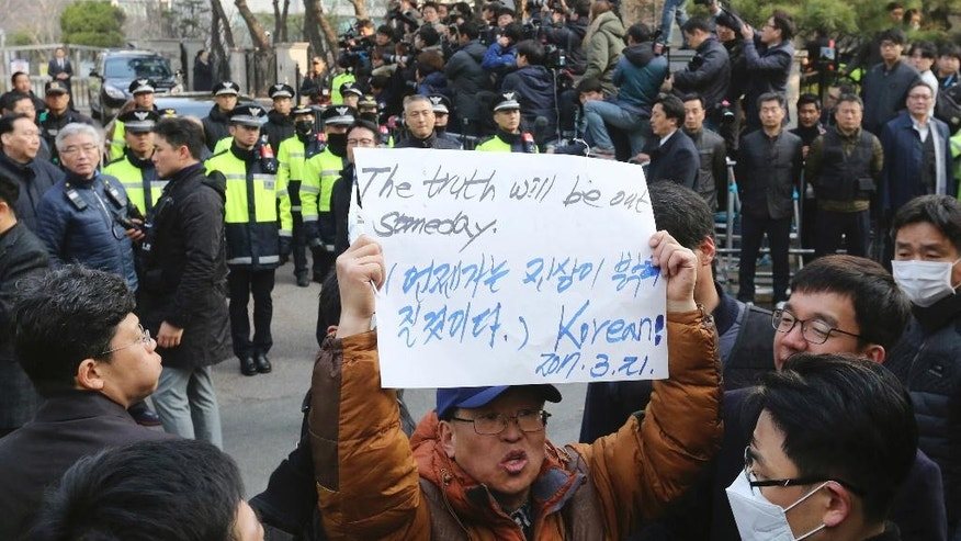 A supporter of ousted South Korean President Park Geun-hye holds up a paper to oppose her impeachment in front of her private home in Seoul, South Korea, Tuesday, March 21, 2017. (AP Photo/Ahn Young-joon).
