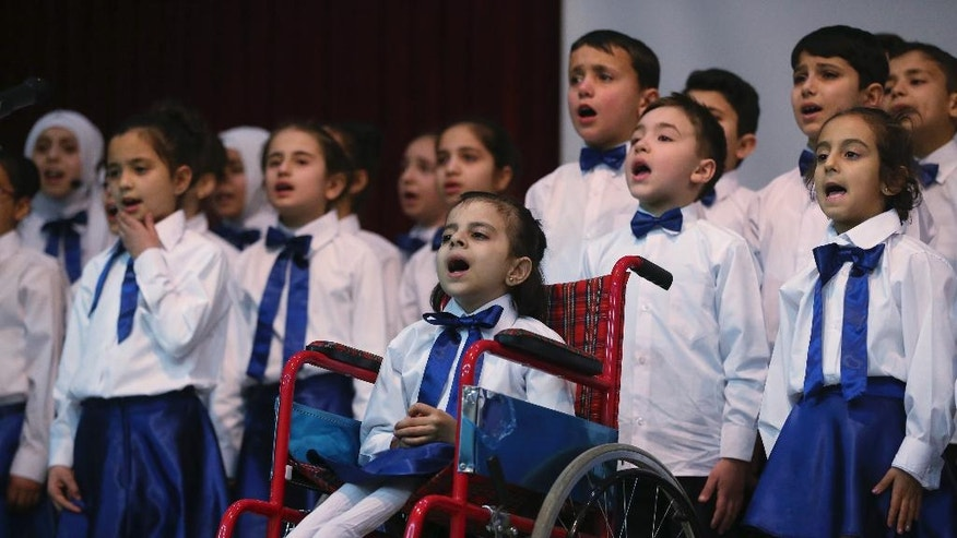 Hibeh, center in wheelchair, a Syrian refugee child from Aleppo performs accompanied by other children during a celebratory ceremony, in Gaziantep, southeastern Turkey, Monday, March 20, 2017. Some Syrians mark March 18 as the anniversary of the uprising against President Bashar Assad, which began six years ago with protests in the southern city of Daraa. Turkey, host to the largest refugee population in the world, including 2.7 million Syrians, is on the front line of the current crisis.(AP Photo/Lefteris Pitarakis)