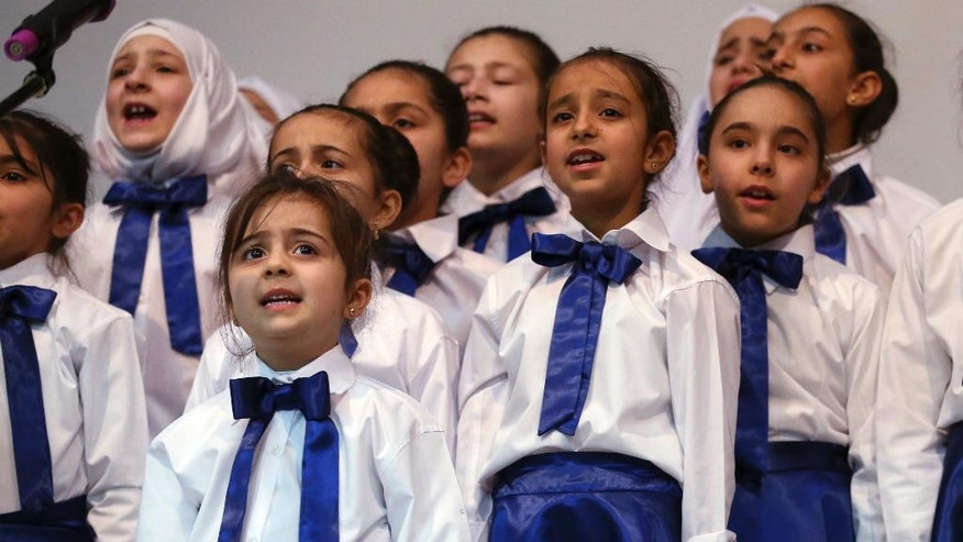 Syrian refugee children perform during a celebratory ceremony, in Gaziantep, southeastern Turkey, Monday, March 20, 2017. Some Syrians mark March 18 as the anniversary of the uprising against President Bashar Assad, which began six years ago with protests in the southern city of Daraa. Turkey, host to the largest refugee population in the world, including 2.7 million Syrians, is on the front line of the current crisis.(AP Photo/Lefteris Pitarakis)