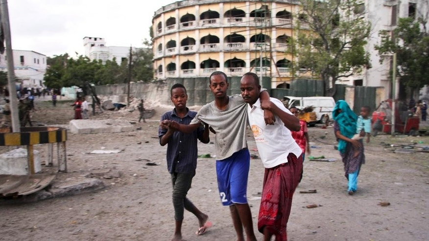 An injured man is assisted after a suicide car bomb attack that targeted a check point in Mogadishu, Somalia, Tuesday, March 21, 2017. The car bomb exploded Tuesday at a military checkpoint near Somalia's presidential palace in the capital after soldiers tried to stop the car and the bomber tried to speed through the checkpoint, killing a number of people, police said. (AP Photo/Farah Abdi Warsameh)