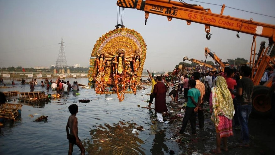 FILE- In this Tuesday, Oct. 11, 2016 file photo, a giant Idol of Hindu goddess Durga suspends from a crane before it is immersed in the River Yamuna during Durga Puja festival in New Delhi, India. A court in northern India has granted the same legal rights as a human to the Ganges and Yamuna rivers, considered sacred by nearly a billion Indians. The Uttaranchal High Court in Uttarakhand state ruled Monday, March 20, 2017,  that the two rivers be accorded the status of living human entities, meaning that if anyone harms or pollutes the rivers, the law would view it as no different from harming a person. (AP Photo/Altaf Qadri, File)