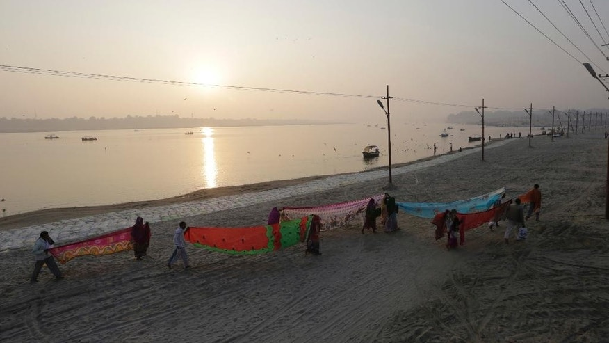 FILE- In this Thursday, Jan. 5, 2017, file photo, Hindu devotees dry their clothes after taking a dip at Sangam, the confluence of rivers Ganges, Yamuna, and mythical Saraswati in Allahabad, India. A court in northern India has granted the same legal rights as a human to the Ganges and Yamuna rivers, considered sacred by nearly a billion Indians. The Uttaranchal High Court in Uttarakhand state ruled Monday, March 20, 2017,  that the two rivers be accorded the status of living human entities, meaning that if anyone harms or pollutes the rivers, the law would view it as no different from harming a person. (AP Photo/Rajesh Kumar Singh, File)