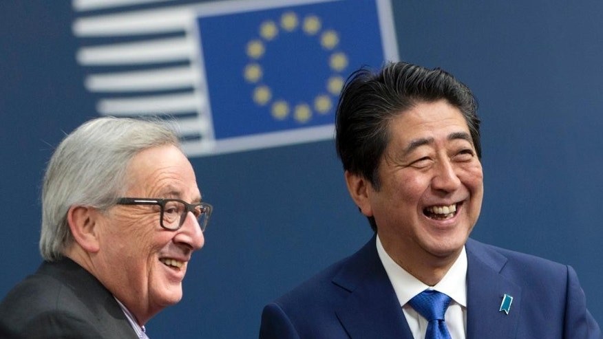 European Commission President Jean-Claude Juncker, left, greets Japanese Prime Minister Shinzo Abe on arrival at the Europa building in Brussels on Tuesday, March 21, 2017. Abe is on a one day visit to meet with EU officials. (AP Photo/Virginia Mayo)