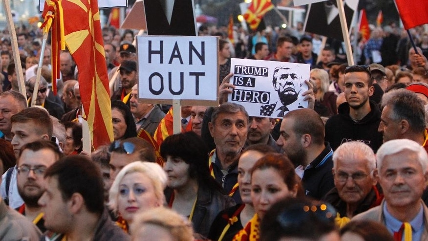 Protesters march through a street in Skopje, Macedonia, on Monday, March 20, 2017. The European Union's enlargement commissioner, Johannes Hahn, has scheduled a visit on Tuesday to Macedonia in another bid to help break a political deadlock that has left the country's parties unable to form a government after December's elections, while thousands of Macedonians protest peacefully for three weeks already against the designation of Albanian as a second official language nationwide. (AP Photo/Boris Grdanoski)