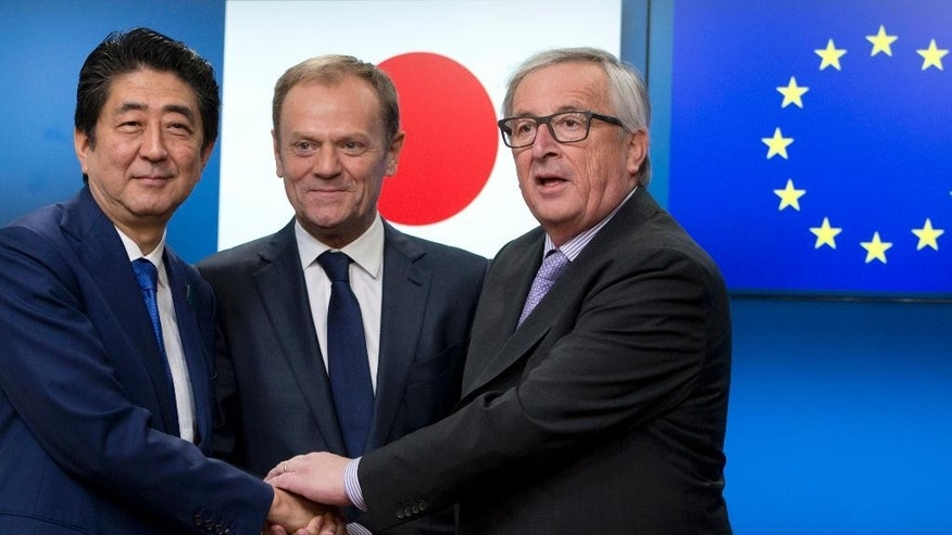 European Commission President Jean-Claude Juncker, right, and European Council President Donald Tusk, center, greet Japanese Prime Minister Shinzo Abe during a meeting at the Europa building in Brussels on Tuesday, March 21, 2017. Abe is on a one day visit to meet with EU officials. (AP Photo/Virginia Mayo)