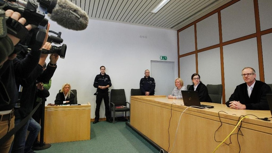 Journalists gather to take pictures of  presiding judge Volker Uhlenbrock, right, in the court room in Essen, Germany, Tuesday, March 21, 2017. The Essen state court has convicted three 17-year-olds of participating in a bomb attack on a Sikh temple last year and given them prison sentences of up to seven years. (Roland Weihrauch/dpa via AP)