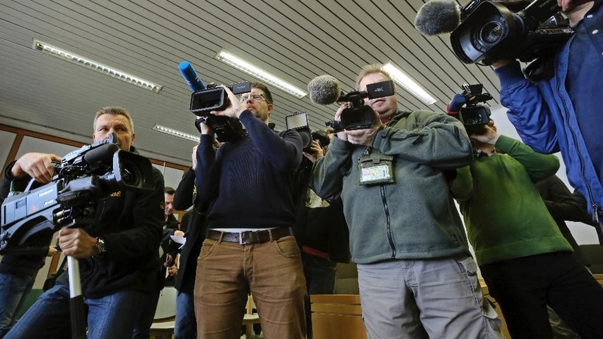 Journalists gather to take pictures of  presiding judge Volker Uhlenbrock, in the court room in Essen, Germany, Tuesday, March 21, 2017. The Essen state court has convicted three 17-year-olds of participating in a bomb attack on a Sikh temple last year and given them prison sentences of up to seven years. (Roland Weihrauch/dpa via AP)