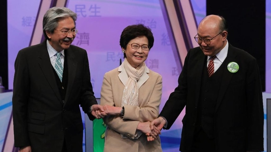 FILE - In this Tuesday, March 14, 2017 file photo, Hong Kong chief executive candidates, from left, former financial secretary John Tsang, former chief secretary Carrie Lam, and former judge Woo Kwok-hing, hold hands together during a photo call before a chief executive election debate in Hong Kong. Hong Kong is poised to select a new leader on March 26, but the choice will be made by a committee of mostly pro-Beijing elites rather than voters from among the city's 7.3 million residents, under a system that was strongly criticized during 2014's huge pro-democracy protests. (AP Photo/Vincent Yu, File)