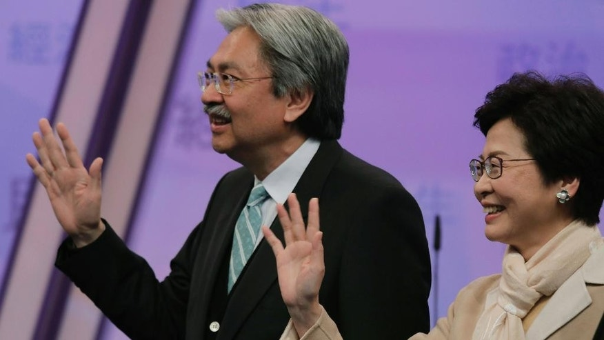 FILE - In this Tuesday, March 14, 2017 file photo, Hong Kong chief executive candidates, former Financial Secretary John Tsang, left, and former chief secretary Carrie Lam wave during a photo call before a chief executive election debate in Hong Kong. Hong Kong is poised to select a new leader on March 26, but the choice will be made by a committee of mostly pro-Beijing elites rather than voters from among the city's 7.3 million residents, under a system that was strongly criticized during 2014's huge pro-democracy protests. (AP Photo/Vincent Yu, File)