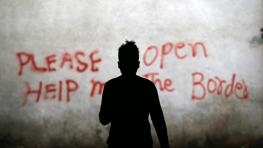 A migrant walks through an abandoned warehouse that has served as a make-shift shelter for hundreds of men trying to reach Western Europe, in Belgrade, Serbia, Tuesday, March 21, 2017. Thousands of migrants have been stranded in Serbia looking for ways to reach western Europe. Many have tried several times to cross to Hungary or Croatia. (AP Photo/Darko Vojinovic)