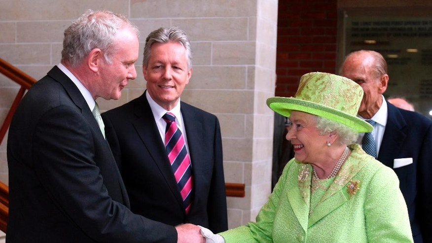 FILE - In this June 27, 2012 file photo Britain's Queen Elizabeth II shakes hands with Northern Ireland Deputy First Minister and former IRA commander Martin McGuinness watched by First minister Peter Robinson, centre, at the Lyric Theatre in Belfast, Northern Ireland. McGuinness, the Irish Republican Army commander who led his underground, paramilitary movement toward reconciliation with Britain, and was Northern Ireland's deputy first minister for a decade in a power-sharing government, has died, his Sinn Fein party announced Tuesday, March 21, 2017, on Twitter. He was 66. (AP Photo/Paul Faith, File)