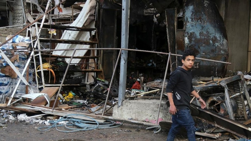 A man walks past  the aftermath of a suicide car bombing in a commercial area in Baghdad's southwestern Amil neighborhood, Iraq, Tuesday, March 21, 2017. A suicide car bombing in Baghdad killed and wounded many people Monday, according to police and medical officials. (AP Photo/Karim Kadim)