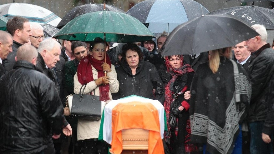 Bernie McGuinness, center, looks at the coffin of her husband Martin as she waits to bring his body back to their home in the bogside area of Londonderry, Northern Ireland, Tuesday, March, 21, 2017. Martin McGuinness, the Irish Republican Army warlord who led his underground, paramilitary movement toward reconciliation with Britain, and was Northern Ireland's deputy first minister for a decade in a power-sharing government, has died, his Sinn Fein party announced Tuesday on Twitter. He was 66.(AP Photo/Peter Morrison)