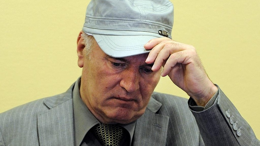 In this Friday, June 3, 2011, image former Bosnian Serb Gen. Ratko Mladic removes his hat in the court room during his initial appearance at the U.N.'s Yugoslav war crimes tribunal in The Hague, Netherlands. Lawyers for former Bosnian Serb military chief Gen. Ratko Mladic say he is seriously ill and could die if he is not provisionally released from custody for treatment while he awaits verdicts in his United Nations trial. (AP Photo/Martin Meissner, Pool)