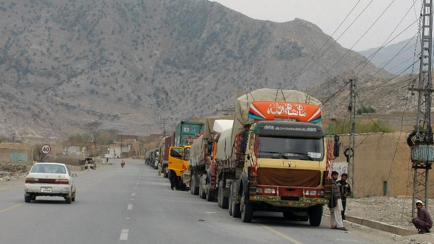 Truck drivers stand beside their trucks while they waiting for border opening at a highway leading to Torkhum, a border crossing between Pakistan Afghanistan, Monday, March, 20, 2017. Pakistan's prime minister ordered the reopening of the country's border with Afghanistan on Monday, ending a protracted closure that has cost businesses on both sides millions of dollars and deepened tensions between the two neighbors. (AP Photo/Matiullah Achakzai)