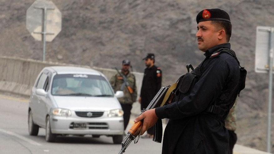 A Pakistani police officer stands guard while his colleagues searching a car at a checkpoint on the highway leading to Torkhum, a border crossing between Pakistan Afghanistan, Monday, March, 20, 2017. Pakistan's prime minister ordered the reopening of the country's border with Afghanistan on Monday, ending a protracted closure that has cost businesses on both sides millions of dollars and deepened tensions between the two neighbors. (AP Photo/Matiullah Achakzai)