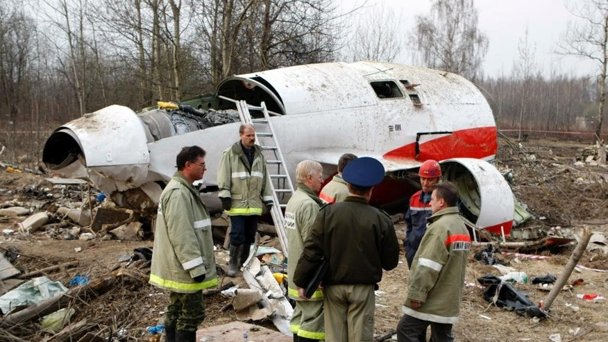 FILE - In this April 13, 2010 file photo, emergency ministry workers stand near the wreckage at the site of the plane crash that killed Polish President Lech Kaczynski in Smolensk, western Russia. Poland's government is accusing European Council President Donald Tusk of betraying national interests and bowing to Moscow in the investigation of the 2010 plane crash in Russia that killed Kaczynski and 95 others. (AP Photo/Mikhail Metzel, File)