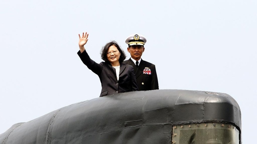 Taiwan's President Tsai Ing-wen, left, waves from a Zwaardvis-class submarine during a visit at Zuoying Naval base in Kaohsiung, southern Taiwan, Tuesday, March 21, 2017. Tsai talks about the plan of manufacturing submarines domestically in a bid to enhance Taiwan's defense capabilities.(AP Photo/ Chiang Ying-ying)