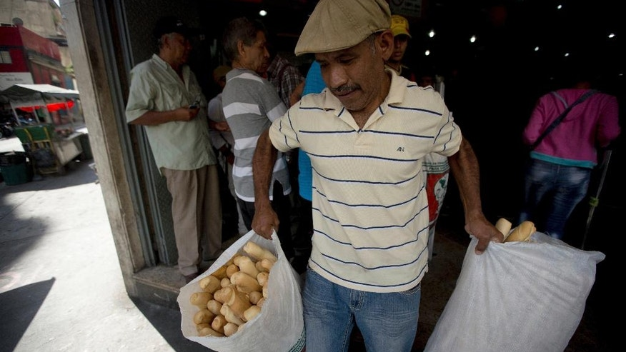 In this March 17, 2017 photo, an employee of the Minka state-run bakery carries bags of bread to be distributed to state-run grocery stores in Caracas, Venezuela. Agents from the National Superintendent of Fair Prices raided Mansion's Bakery last week and accused the owners of hoarding scarce sacks of government-imported flour, saying the subsidized goods should have been used to make price-regulated loaves but instead was turned into more expensive croissants and sweet rolls.  (AP Photo/Fernando Llano)