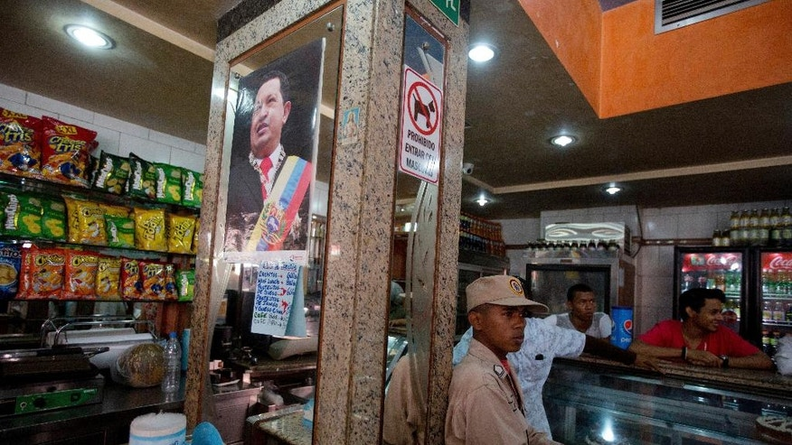 In this March 20, 2017 photo, a militia member stands guard next to a poster of late Venezuelan President Hugo Chavez, at a private bakery that was taken over by the government in Caracas, Venezuela. Within hours of the handover, the new storekeepers took down the Coca-Cola-sponsored sign outside and hung up photos of Maduro, Chavez and South American independence hero Simon Bolivar. (AP Photo/Fernando Llano)