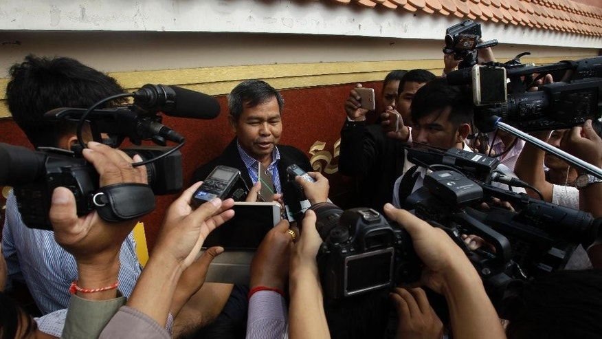 Yung Phanith, center, lawyer to Oeut Ang, center, gives a press conference at Phnom Penh Municipal Court, in Phnom Penh, Cambodia, Thursday, March 23, 2017. Cambodian court has sentenced the man to life in prison for killing a prominent government critic. (AP Photo/Heng Sinith)
