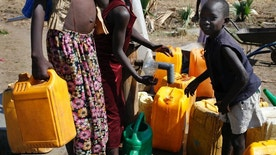 In this photo taken Sunday, March 19, 2017, children take water from a well at a camp for those who were previously displaced by fighting, near a church in Rajaf, South Sudan. As the world marks World Water Day on Wednesday, March 22, 2017 more than 5 million people in South Sudan do not have access to safe, clean water, compounding the problems of famine and civil war, according to UNICEF. (Matthieu Alexandre/Caritas Internationalis via AP)