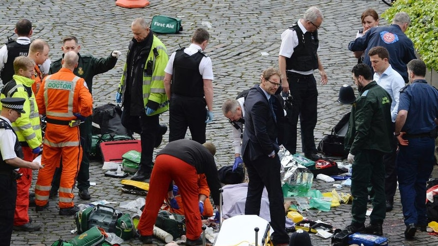 "Conservative MP Tobias Ellwood, centre, stands amongst the emergency services at the scene outside the Palace of Westminster, London, Wednesday, March 22, 2017.  London police say they are treating a gun and knife incident at Britain's Parliament ""as a terrorist incident until we know otherwise."" The Metropolitan Police says in a statement that the incident is ongoing. It is urging people to stay away from the area. Officials say a man with a knife attacked a police officer at Parliament and was shot by officers. Nearby, witnesses say a vehicle struck several people on the Westminster Bridge.  (Stefan Rousseau/PA via AP)."