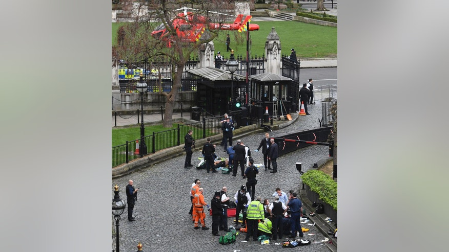 "Emergency services attend to injured people outside the Palace of Westminster, London, Wednesday, March 22, 2017.  London police say they are treating a gun and knife incident at Britain's Parliament ""as a terrorist incident until we know otherwise."" The Metropolitan Police says in a statement that the incident is ongoing. It is urging people to stay away from the area. Officials say a man with a knife attacked a police officer at Parliament and was shot by officers. Nearby, witnesses say a vehicle struck several people on the Westminster Bridge.  (Stefan Rousseau/PA via AP)."