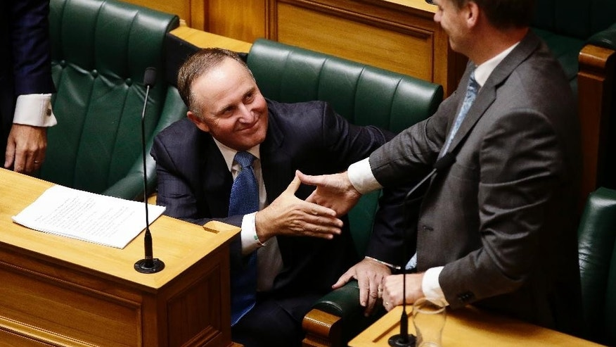 Former New Zealand Prime Minister John Key, left, shakes hands with his successor Prime Minister Bill English following his valedictory speech to parliament in Wellington, New Zealand, Wednesday, March 22, 2017. Key was leader for eight years before resigning in December. (AP Photo/Mark Baker)