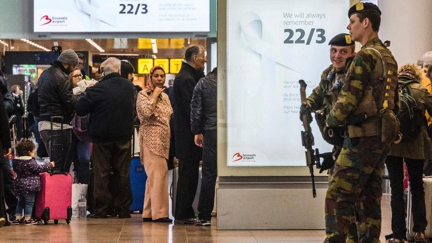 Soldiers patrol as passengers walk through the departure terminal during the one-year anniversary service at Zaventem Airport in Brussels on Wednesday, March 22, 2017. The suicide bombings at the Brussels airport and subway on March 22, 2016, killed 32 people and wounded more than 300 others. (AP Photo/Geert Vanden Wijngaert)