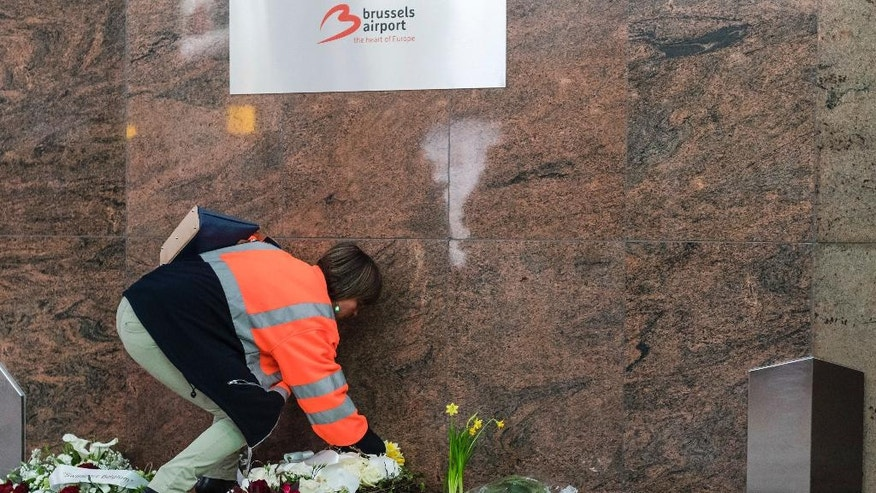 A Brussels Airport workers lays flowers at a memorial, marking the one-year anniversary at Zaventem Airport in Brussels on Wednesday, March 22, 2017. The suicide bombings at the Brussels airport and subway on March 22, 2016, killed 32 people and wounded more than 300 others. (AP Photo/Geert Vanden Wijngaert)